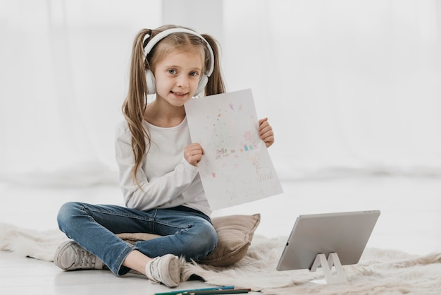 Garota frequentando aulas virtuais e segurando um desenho