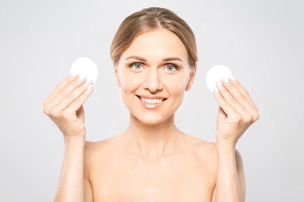 Garota fresca e saudável, removendo a maquiagem do rosto com uma almofada de algodão. mulher de beleza limpando o rosto com uma almofada de algodão isolada no fundo branco isolado. conceito de cuidados com a pele e beleza.