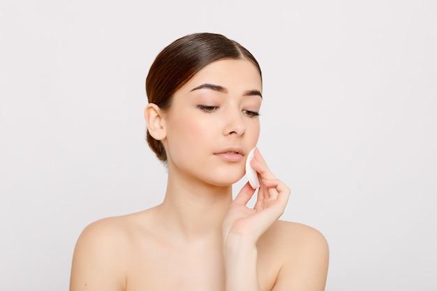 Garota fresca e saudável, removendo a maquiagem do rosto com uma almofada de algodão. mulher de beleza limpando o rosto com uma almofada de algodão isolada no fundo cinza. cuidados com a pele e conceito de beleza.