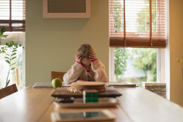 Garota frustrada sentada à mesa e estudando na sala de estar