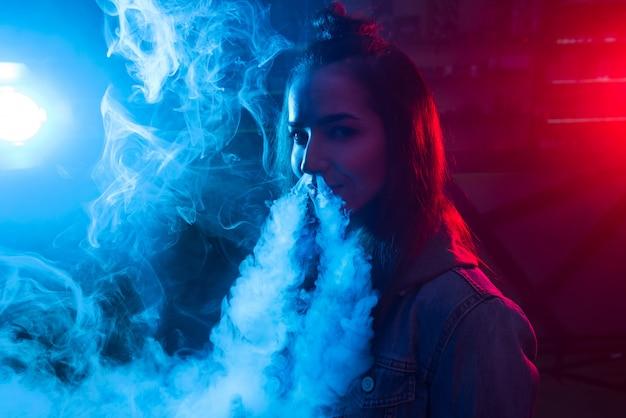 Garota fuma um cigarro e solta fumaça em uma boate.