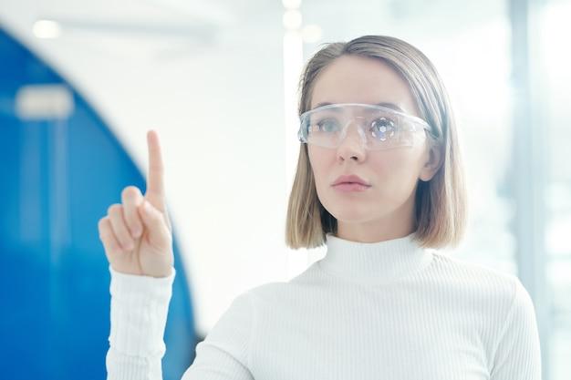 Garota futurista usando óculos inteligentes enquanto analisa informações no escritório