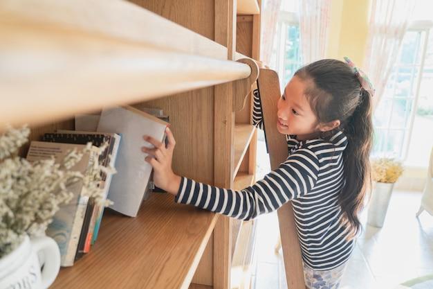 Garota garoto asiático escolher o livro da prateleira
