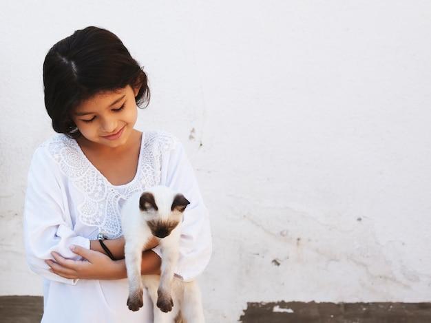 Garota garoto bonito segurando nas mãos um lindo gato siamês