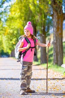 Garota garoto caminhadas com bengala e mochila no outono
