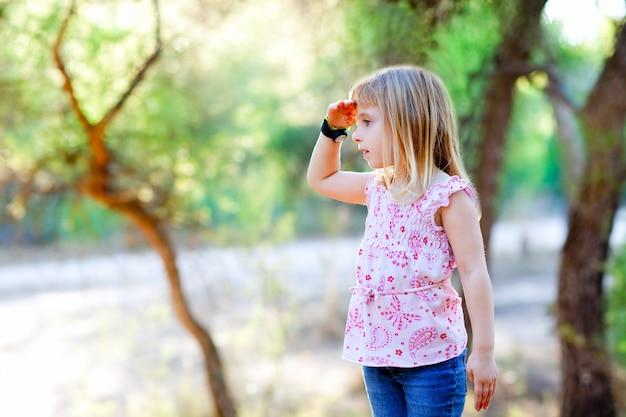 Garota garoto caminhadas, procurando a mão na cabeça na floresta
