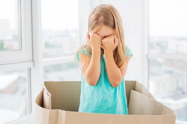 Garota garoto cobrindo o rosto com os punhos na caixa