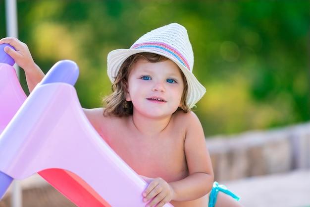 Garota garoto de bebê com chapéu no verão no campo verde