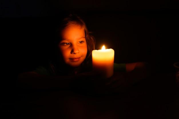 Garota garoto de sete anos de idade admira uma vela acesa de cera à noite em casa