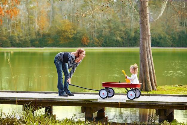 Garota garoto e mãe andando no lago com carrinho de puxar