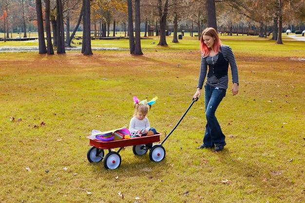 Garota garoto e mãe andando no parque com carrinho de puxar