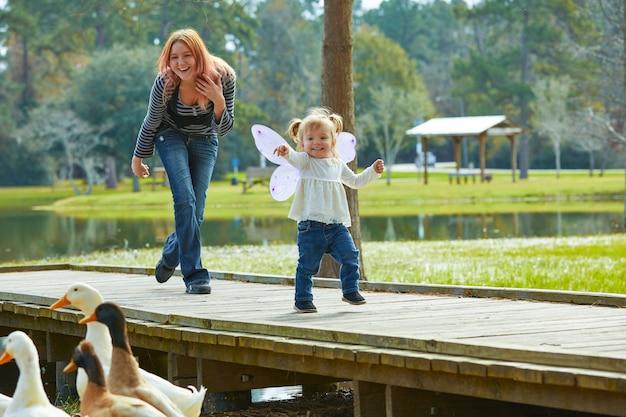 Garota garoto e mãe brincando com patos no lago