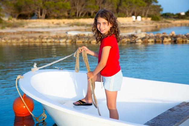 Garota garoto fingindo ser marinheiro na proa do barco em formentera
