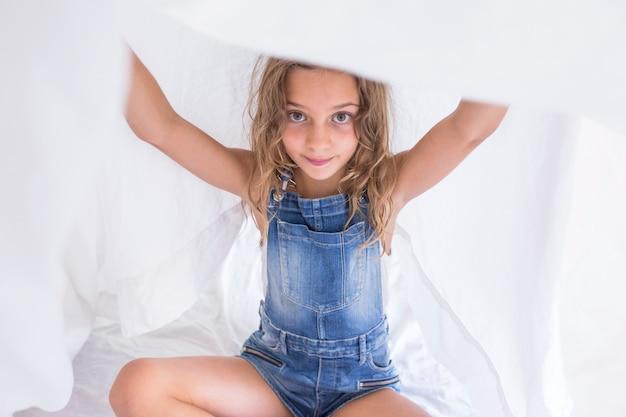 Garota garoto lindo jogando sob lençóis brancos na cama. diversão em ambientes fechados. estilo de vida e amor em família