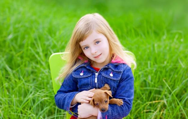 Garota garoto loiro com cachorro de estimação na grama verde