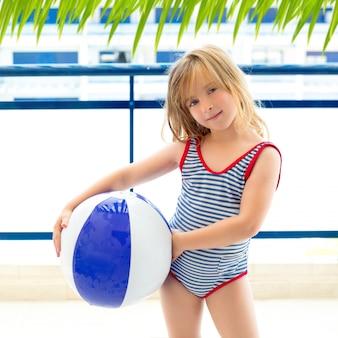 Garota garoto loiro com maiô com bola de verão azul
