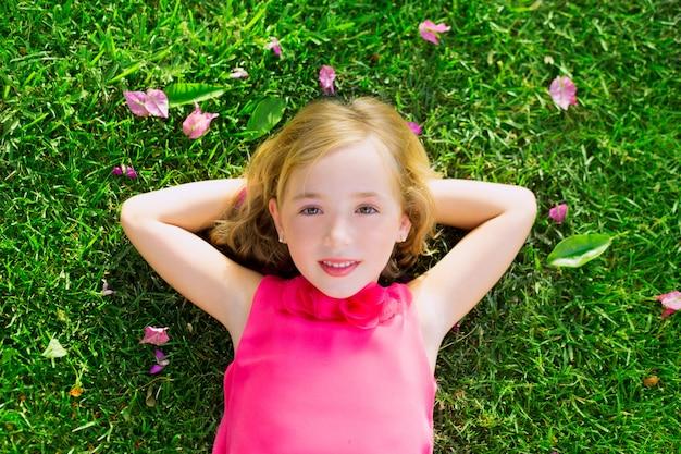 Garota garoto loiro deitado na grama do jardim sorrindo vista aérea