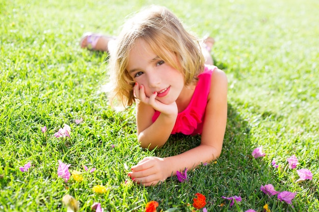 Garota garoto loiro deitado relaxado na grama do jardim com flores