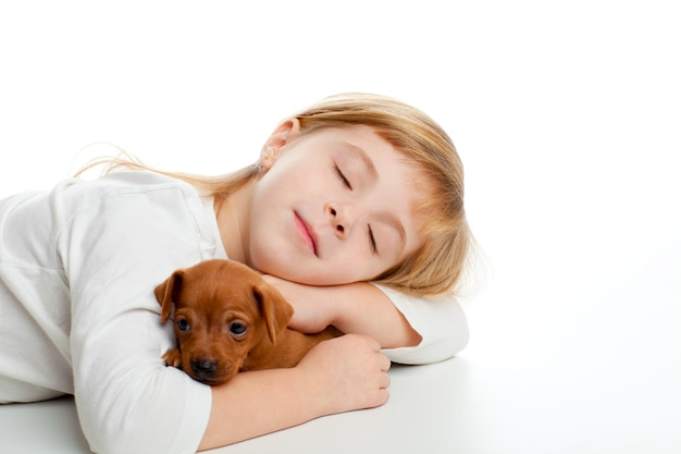 Garota garoto loiro dormindo com mini pinscher pet