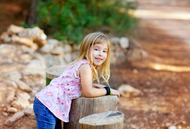 Garota garoto loiro na floresta de tronco de árvore