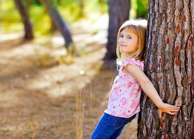 Garota garoto loiro no tronco de árvore outono