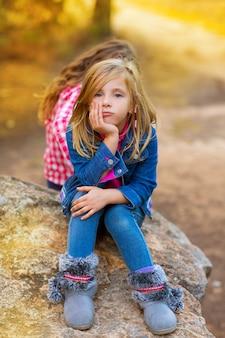 Garota garoto loiro pensativo entediado na floresta ao ar livre