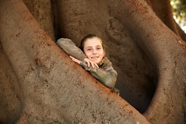 Garota garoto loiro sorrindo braços na grande árvore de ficus