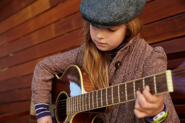 Garota garoto loiro tocando guitarra com boina de inverno