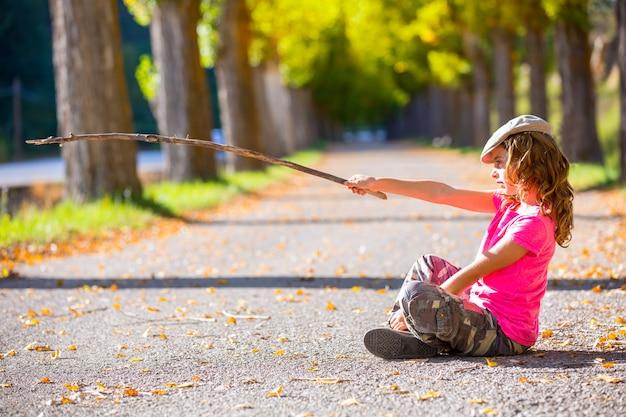 Garota garoto outono com calças de camuflagem, sentado na trilha de árvores