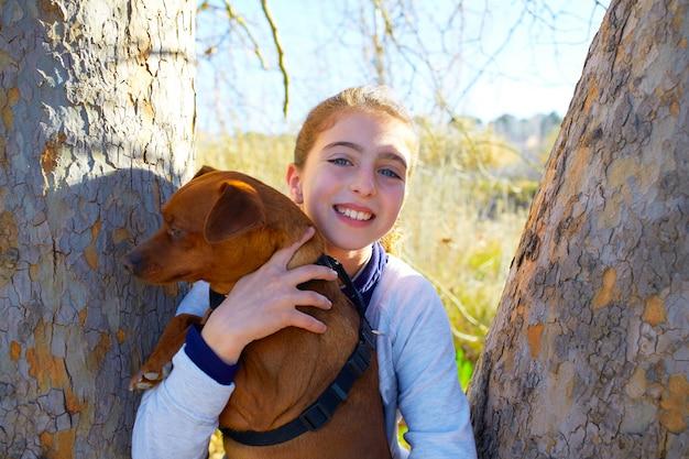 Garota garoto outono com cão de estimação relaxado na floresta de outono