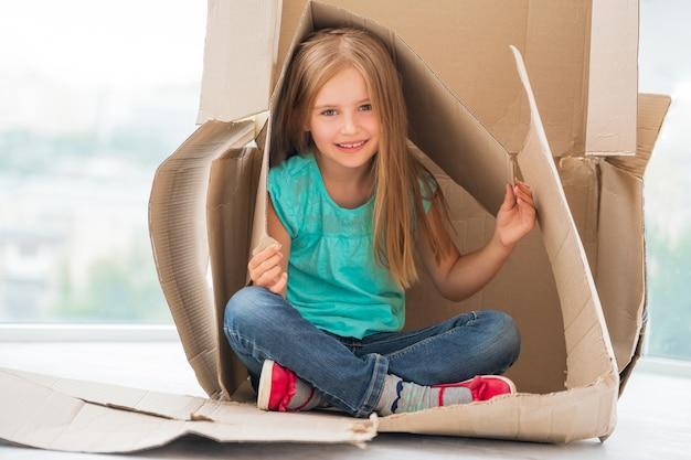 Garota garoto pequeno sentado na casa de papelão