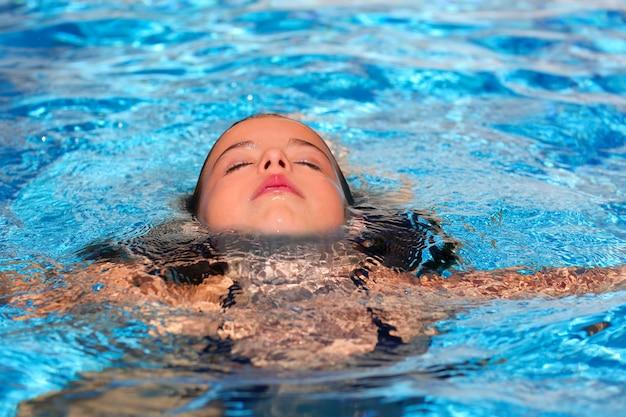 Garota garoto relaxado no rosto de piscina na superfície da água