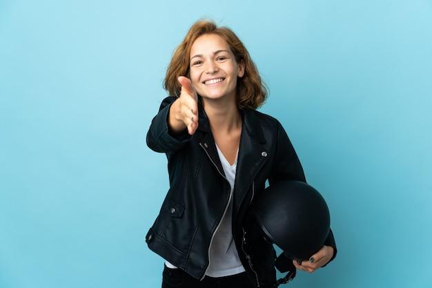 Garota georgiana segurando um capacete de motociclista isolado em um fundo azul apertando as mãos para fechar um bom negócio
