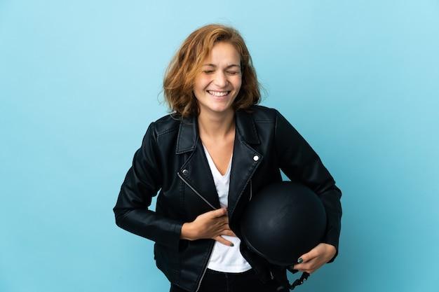 Garota georgiana segurando um capacete de motociclista isolado em uma parede azul e sorrindo muito