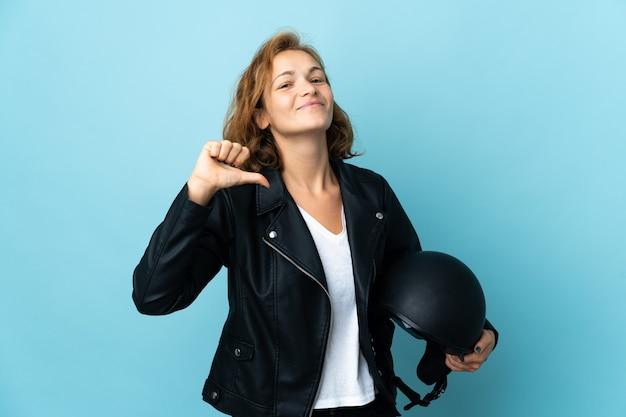Garota georgiana segurando um capacete de motociclista isolado em uma parede azul, orgulhosa e satisfeita