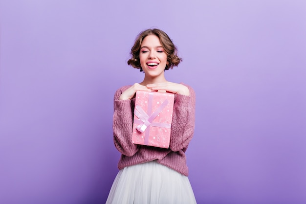 Garota glamorosa com cabelo curto encaracolado, posando com caixa de presente rosa e rindo. modelo feminino atraente com presente de natal, isolado na parede roxa e sorrindo.