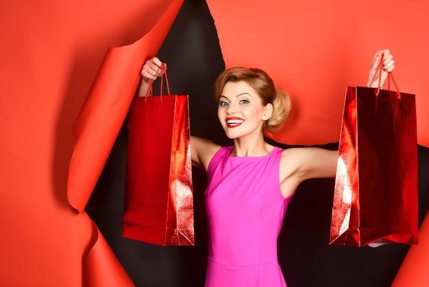 Garota glamorosa com maquiagem perfeita, lábios vermelhos emergindo do papel vermelho segurando sacolas de compras nas mãos