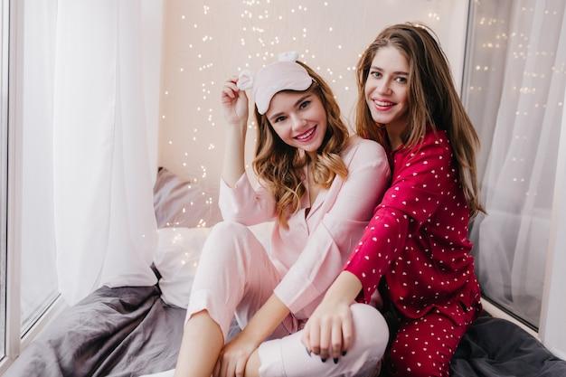 Garota glamorosa com máscara rosa posando com sorriso interessado na cama dela. retrato interior de encantadoras modelos femininas de pijama, relaxando no fim de semana juntos.