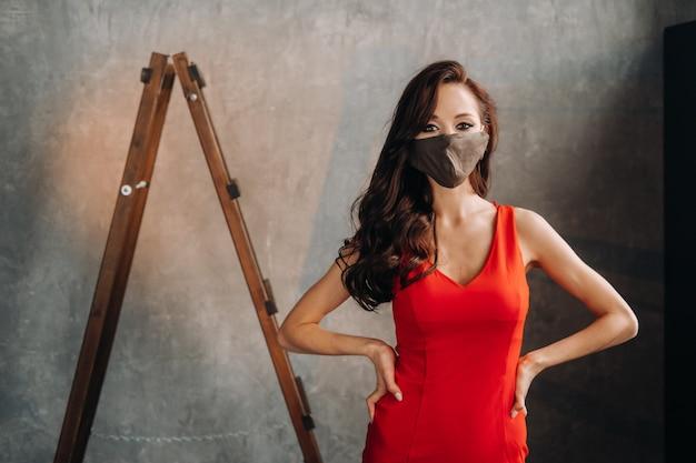 Garota glamorosa em um vestido vermelho e uma máscara protetora em um fundo vintage