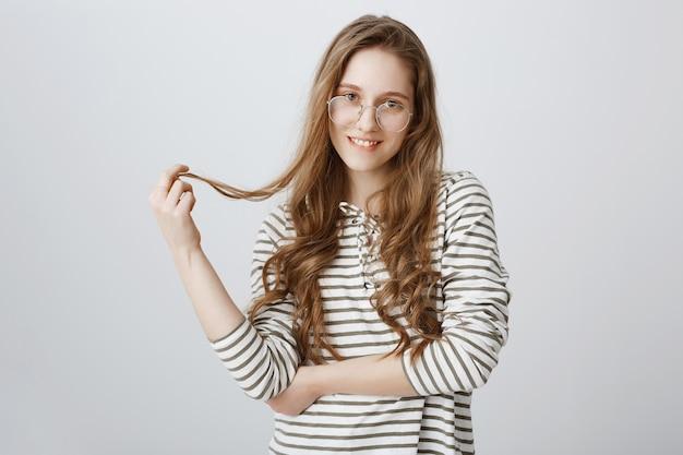 Garota glamour de óculos, brincando com o cabelo coquete