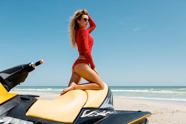 Garota glamour em traje de banho na scooter de água. cabelo loiro comprido de modelo de biquíni de corpo perfeito. esportes aquáticos, estilo de vida de verão. oceano azul no fundo.