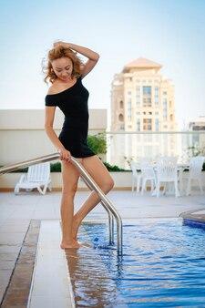 Garota glamour em um vestido coquetel perto da piscina na cobertura