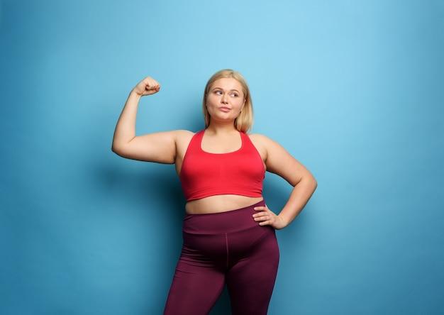 Garota gorda faz ginástica em casa. expressão pensativa.