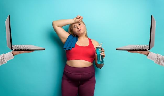 Garota gorda faz ginástica em casa remotamente com o laptop. expressão cansada.