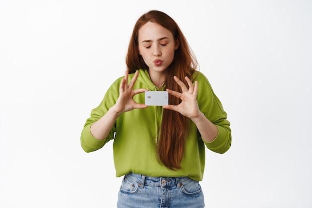 Garota gosta de fazer compras, beijar o cartão de crédito com os olhos fechados, comprar algo, pagar pela compra, fazer pedidos online em branco.