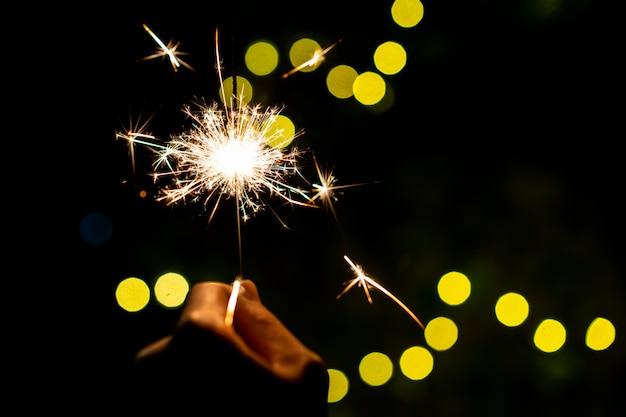 Garota gosta de jogar um fogos de artifício de mão pequeno diamante, comemorando no festival de natal e ano novo.