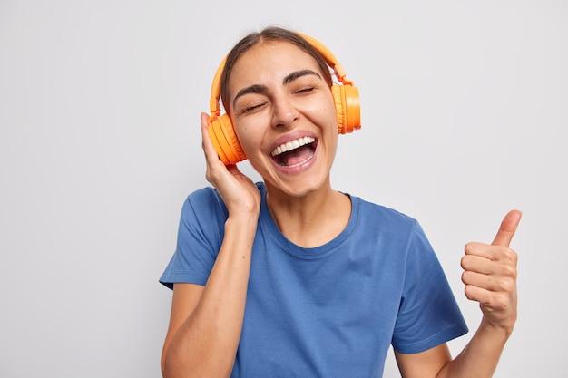 Garota gosta de música favorita mantém polegar para cima gosta de melodia favorita em poses de fone de ouvido no branco
