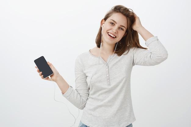 Garota gosta de trabalhar com fones de ouvido nos ouvidos. mulher europeia alegre fofa e despreocupada tocando o cabelo, inclinando a cabeça suavemente, sorrindo alegremente, ouvindo música nos fones de ouvido, segurando um smartphone, mostrando a tela do gadget