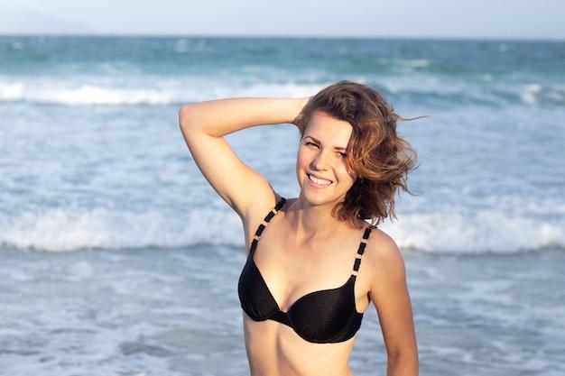 Garota gostosa sexy de biquíni, mulher bonita feliz positiva jovem curtindo férias no mar, praia, nadar no oceano, sorrindo para o dia ensolarado de verão