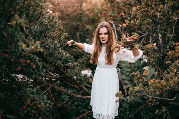 Garota gótica no vestido branco vintage posando contra arbustos no parque de verão.